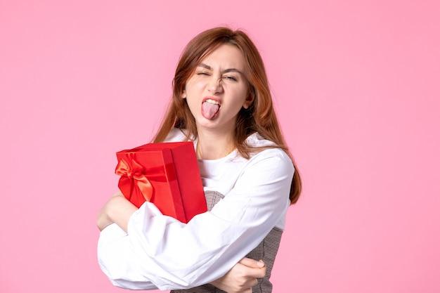 Вид спереди молодая женщина с подарком в красной упаковке на розовом фоне, свидание, марш, горизонтальная женщина, чувственное равенство