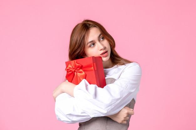Вид спереди молодая женщина с подарком в красном пакете на розовом фоне, свидание, марш, любовь, женщина, чувственное равенство