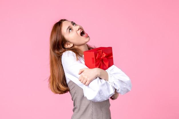 Вид спереди молодая женщина с подарком в красном пакете на розовом фоне, свидание в любви, марш, горизонтальная женщина чувственного равенства