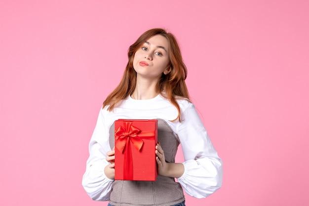Вид спереди молодая женщина с подарком в красной упаковке на розовом фоне свидание любви марш горизонтальный чувственный подарок духи женщина фото равенство