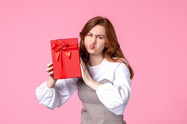 Вид спереди молодая женщина с подарком в красной упаковке на розовом фоне свидание любви марш горизонтальные чувственные подарки духи равенство женщина фото деньги