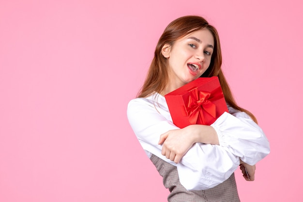 Front view young female with present in red package on pink background love date march sensual equality woman