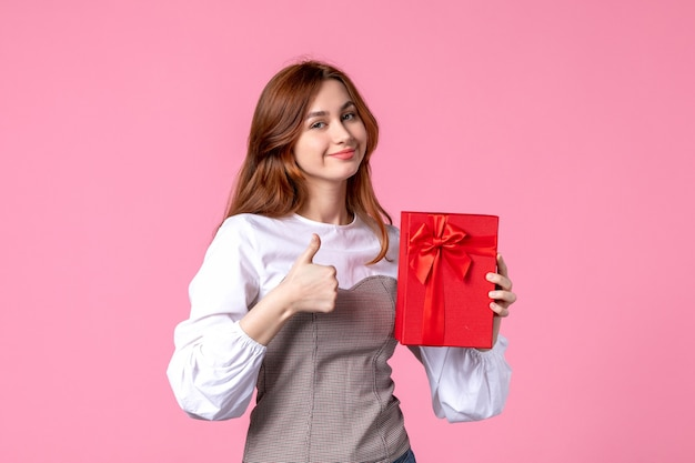 Front view young female with present in red package on pink background march money horizontal sensual woman perfume gift