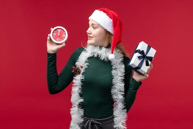 Вид спереди молодая женщина с подарками с часами на красном фоне