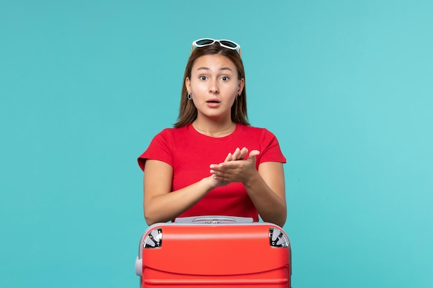 Front view young female with red bag applauding on blue space