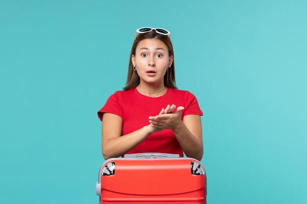 Вид спереди молодая женщина с красной сумкой, аплодирующая на синем пространстве