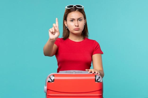 Giovane femmina di vista frontale con il sacchetto rosso sullo spazio blu
