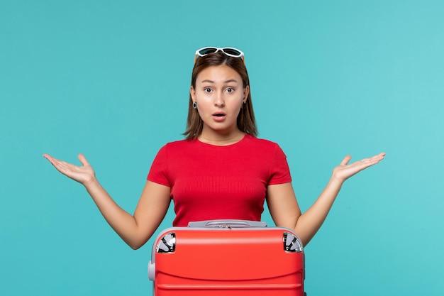 빨간 가방이 푸른 공간에서 휴가를 준비하는 전면보기 젊은 여성