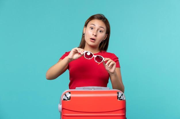 Вид спереди молодая женщина с красной сумкой, готовящаяся к отпуску на синем этаже, поездка, путешествие, путешествие, цвет женщины