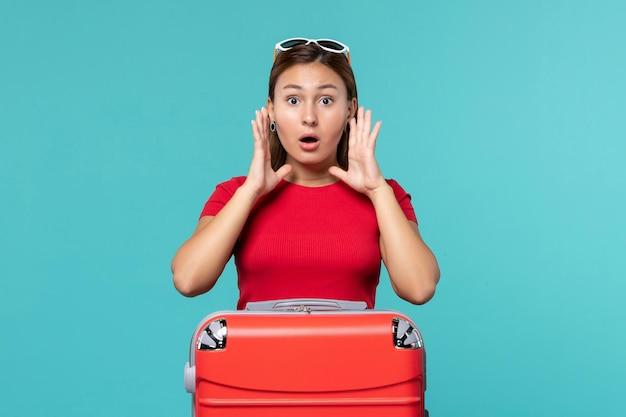 正面図水色の空間で休暇の準備をしている赤いバッグを持つ若い女性