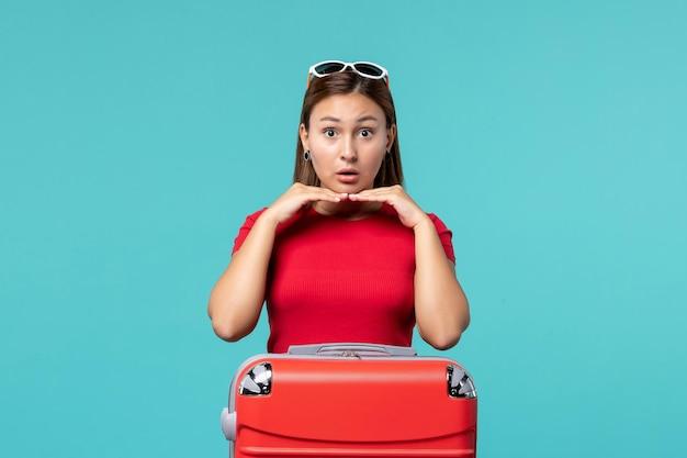 青いスペースで休暇の準備をしている赤いバッグを持つ若い女性の正面図