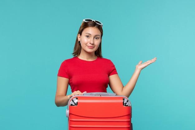 Giovane femmina di vista frontale con il sacchetto rosso che si prepara per la vacanza sullo spazio blu