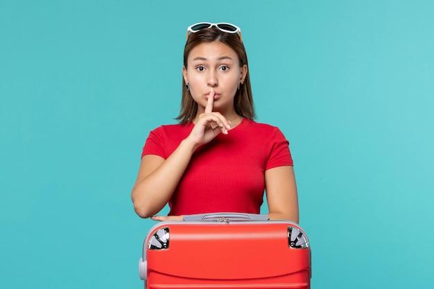 Giovane femmina di vista frontale con la borsa rossa che si prepara per la vacanza che mostra il segno tranquillo sullo spazio blu