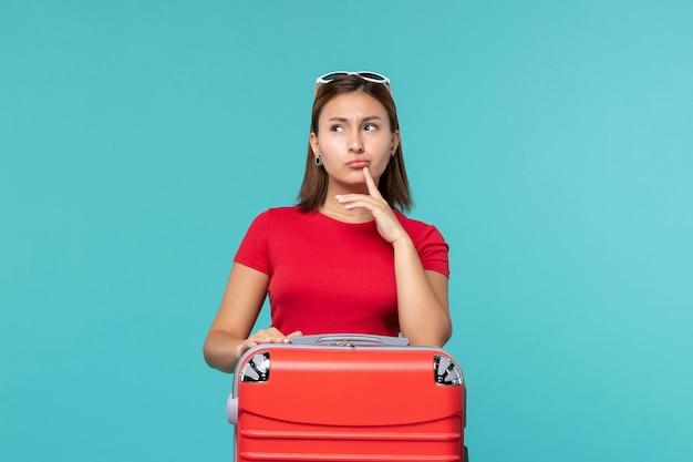 Giovane femmina di vista frontale con il sacchetto rosso che si prepara per le vacanze e pensa sullo spazio blu