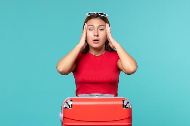 青いスペースに頭痛を持っている赤いバッグを持つ若い女性の正面図