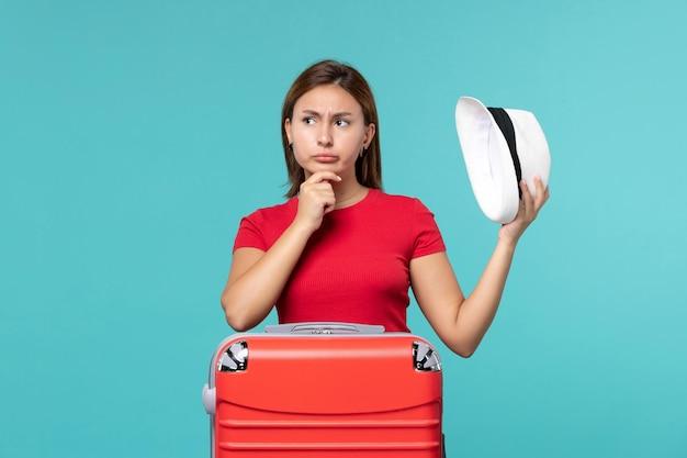 彼女の帽子を保持し、青い空間を考えて赤いバッグを持つ若い女性の正面図