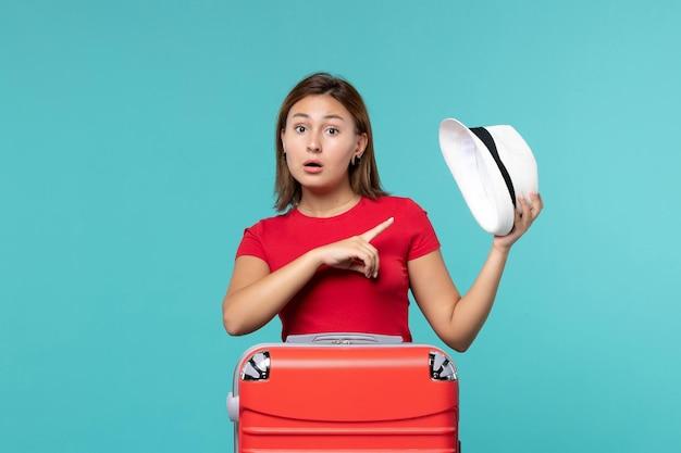 青いスペースに彼女の帽子を保持している赤いバッグを持つ若い女性の正面図