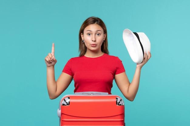 Вид спереди молодая женщина с красной сумкой, держащая шляпу на синем пространстве