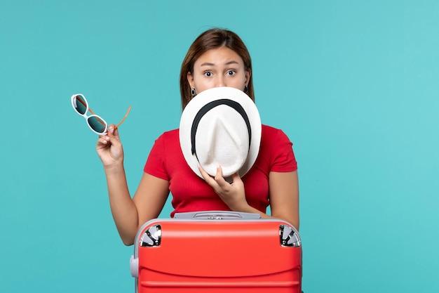 青い机の上に彼女のサングラスと帽子を保持している赤いバッグを持つ若い女性の正面図