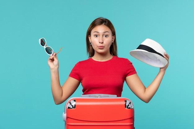 青いスペースにサングラスと帽子を保持している赤いバッグを持つ若い女性の正面図