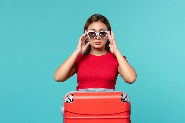 Giovane femmina di vista frontale con il sacchetto rosso che tiene i suoi occhiali da sole sullo spazio blu-chiaro