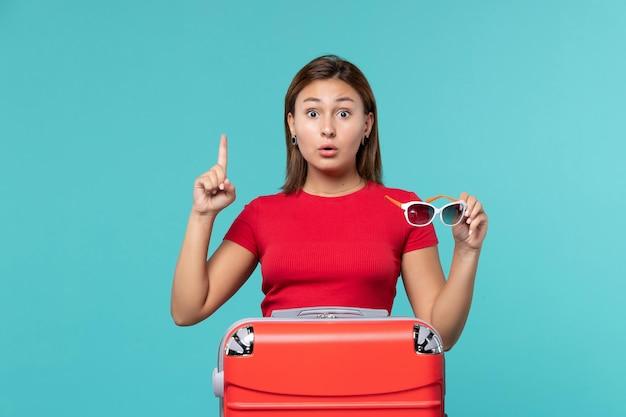 Вид спереди молодая женщина с красной сумкой, держащая солнцезащитные очки на синем столе