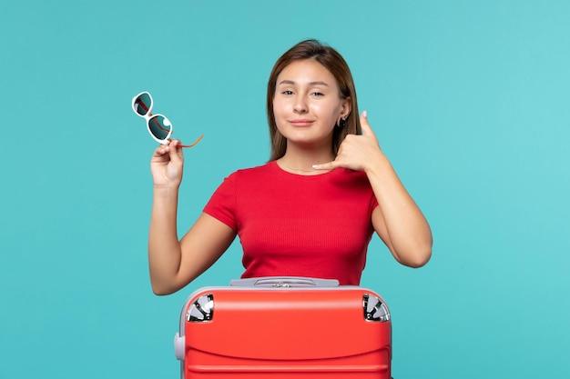 푸른 공간에 그녀의 선글라스를 들고 빨간 가방 전면보기 젊은 여성