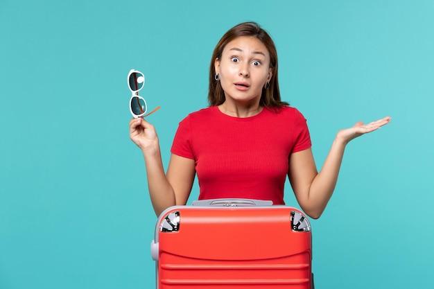 正面図水色のスペースにサングラスを保持している赤いバッグを持つ若い女性