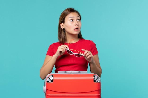 青いスペースにサングラスを保持している赤いバッグを持つ若い女性の正面図