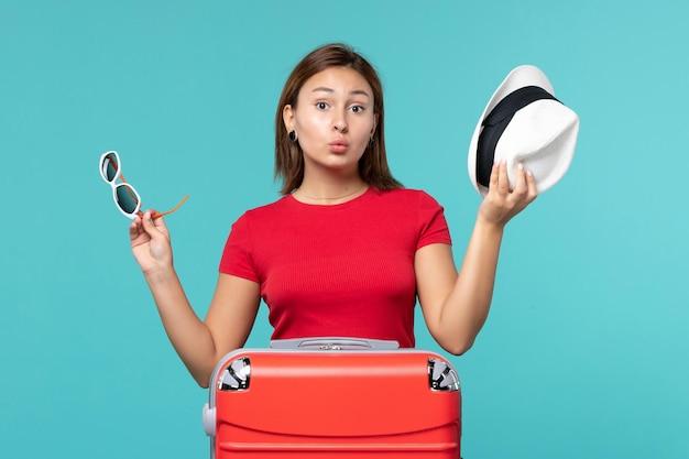 青いスペースに帽子とサングラスを保持している赤いバッグを持つ若い女性の正面図