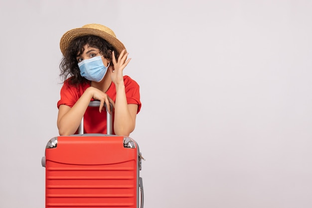 Вид спереди молодая женщина с красной сумкой в маске на белом фоне цвета солнца пандемический туристический вирус covid