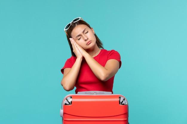 青いスペースで眠っているポーズで赤いバッグを持つ若い女性の正面図