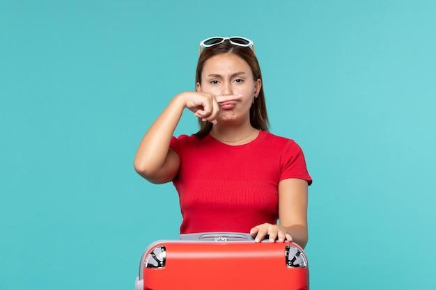 Вид спереди молодая женщина с красной сумкой, делая смешное лицо на синем пространстве