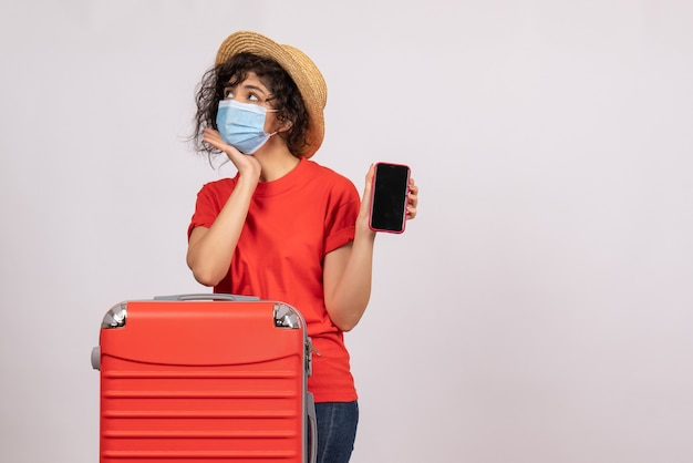 Vista frontale giovane donna con borsa rossa in maschera che tiene il telefono su uno sfondo bianco sole covid pandemia vacanza viaggio turistico virus colore