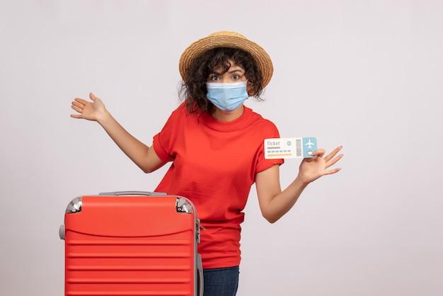 Vista frontale giovane donna con borsa rossa in maschera che tiene biglietto su sfondo bianco sole covid pandemia vacanza viaggio colore turistico