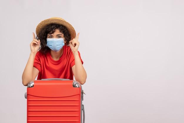 Vista frontale giovane donna con borsa rossa in maschera su sfondo bianco colore del sole covid pandemia viaggio virus turistico