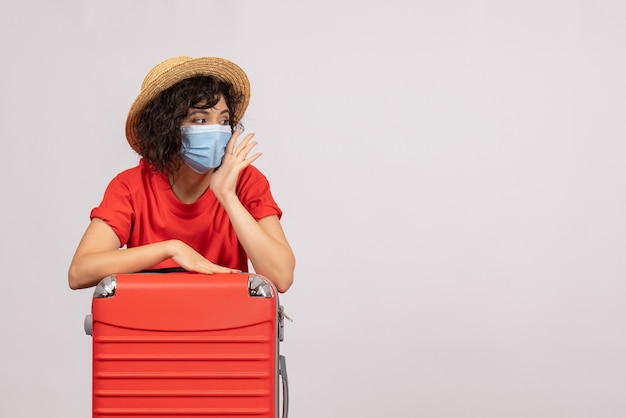 Front view young female with red bag in mask on white background sun color covid- pandemic vacation tourist virus