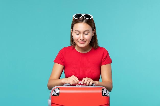Вид спереди молодая женщина с красной сумкой на голубом пространстве