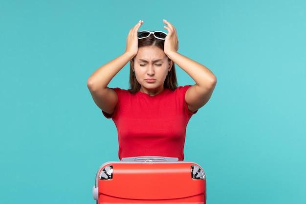 正面図水色のスペースに赤いバッグを持つ若い女性