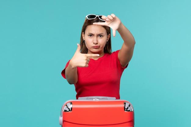 Giovane femmina di vista frontale con la borsa rossa che posa sullo spazio blu