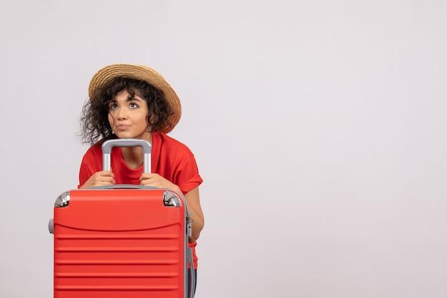 Вид спереди молодая женщина с красной сумкой, готовящаяся к поездке на белом фоне, самолет путешествия солнца, туристический отдых, цветной отдых, полет