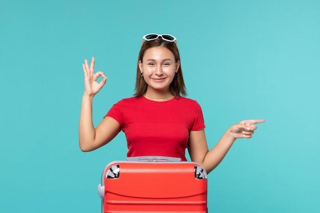 青いスペースに笑みを浮かべて休暇の準備をしている赤いバッグを持つ若い女性の正面図