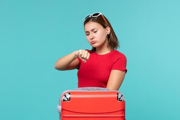 青いスペースで時間をチェックする休暇の準備をしている赤いバッグを持つ若い女性の正面図