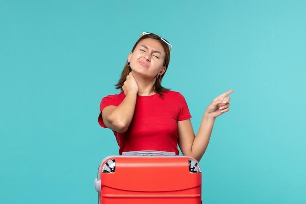 青いスペースに首の痛みを持って休暇の準備をしている赤いバッグを持つ若い女性の正面図