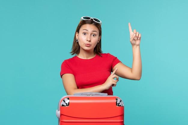푸른 공간에 휴가를 준비하는 빨간 가방 전면보기 젊은 여성
