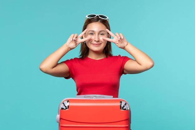 青い机の上で休暇の準備をしている赤いバッグを持つ若い女性の正面図