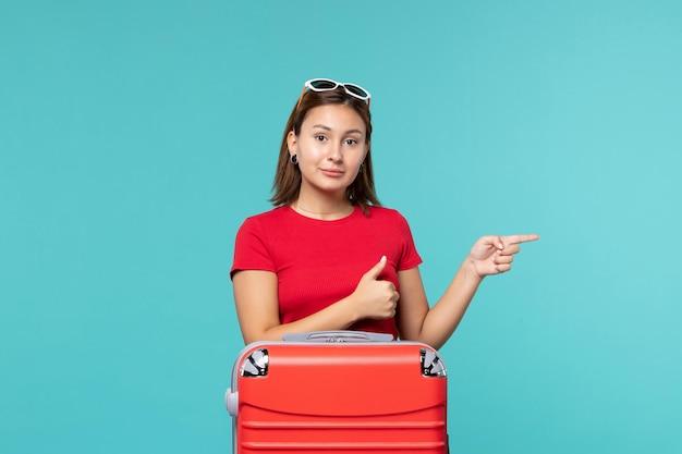 Вид спереди молодая женщина с красной сумкой, готовящаяся к отпуску на синем полу, цветное путешествие, путешествие, путешествие, женщина