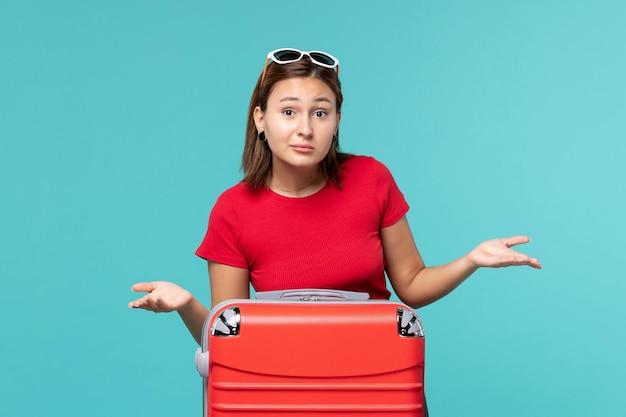 Вид спереди молодая женщина с красной сумкой, готовящаяся к отпуску на синем полу, путешествие, путешествие, женщина, путешествие на море