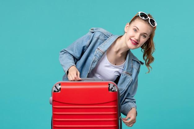 Вид спереди молодая женщина с красной сумкой готовится к отпуску на синем пространстве