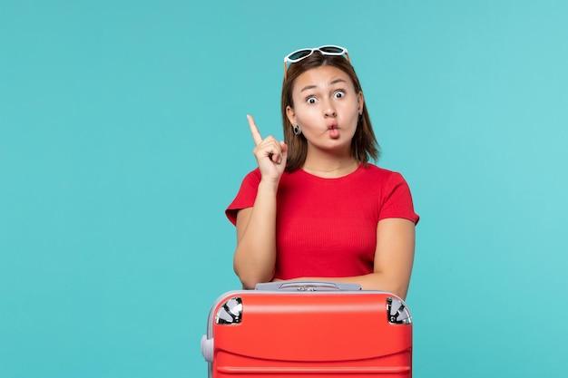 水色の空間で休暇の準備をしている赤いバッグを持つ若い女性の正面図
